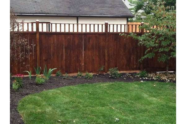 Dark wood fence along side of house and enclosing lawn.